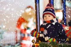 转盘的小孩男孩在圣诞节市场上 免版税图库摄影