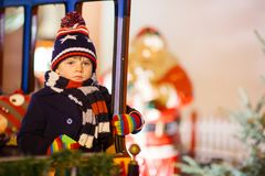 转盘的小孩男孩在圣诞节市场上 免版税库存图片