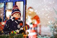 转盘的小孩男孩在圣诞节市场上 库存图片
