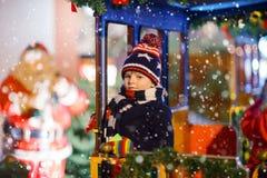 转盘的小孩男孩在圣诞节市场上 图库摄影