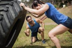 翻转轮胎的适合的妇女,当欢呼在障碍桩期间时的教练员 免版税库存图片