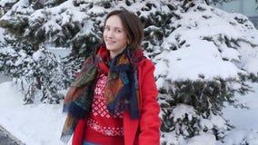 转过来在红色外套的年轻微笑的深色的女孩与围巾在冬天森林风景背景上把她的手放  股票视频
