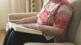 翻转通过厚实的书的页的老妇人 影视素材