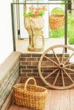 轮子、篮子和花在门廊经典之作门面 免版税库存照片