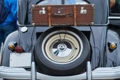 轮子和手提箱在一辆老汽车的后车箱 库存照片