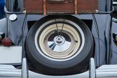 轮子和手提箱在一辆老汽车的后车箱 库存图片
