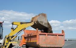 轮子挖掘机装货石渣堆 库存照片