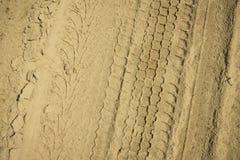 轮子的踪影在黄沙的 背景理想的沙子纹理 库存照片