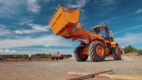 轮子继续前进建造场所的装载者挖掘机 大量的打瞌睡的人 股票录像