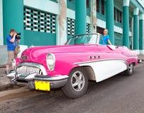 轮子老美国减速火箭的汽车的(上个世纪的第50岁月),偶象视域美丽的妇女在城市,马莱克的 库存照片
