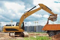 轮子装入程序挖掘机和卸车倾销者 免版税库存照片