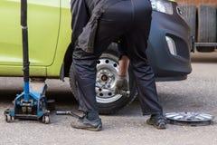 轮子,一辆残破的汽车的轮胎修理从技工的 库存图片