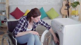 轮椅主妇的美丽的年轻残疾妇女洗涤衣裳 影视素材