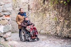 轮椅和儿子的资深父亲步行的在老镇 免版税库存照片