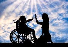 轮椅和她的妈妈的愉快的残疾儿童女孩 免版税图库摄影