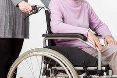 轮椅和她的监护人的夫人 库存图片