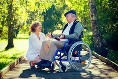 轮椅和少妇的老人在公园 免版税库存照片