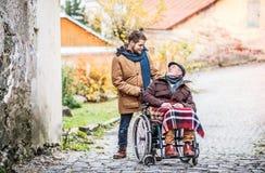 轮椅和年轻儿子的资深父亲步行的 图库摄影