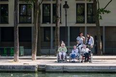 轮椅和他们的年轻助手的老残疾妇女 免版税库存照片