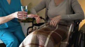 轮椅拒绝的沮丧的病的妇女采取从护士,特写镜头的医学 股票视频