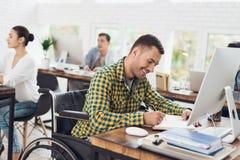轮椅的一个人写与笔在笔记本 他在一个明亮的办公室工作 免版税库存照片