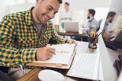 轮椅的一个人写与笔在笔记本 他在一个明亮的办公室工作 库存图片