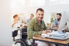 轮椅的一个人写与笔在笔记本 他在一个明亮的办公室工作 免版税库存图片