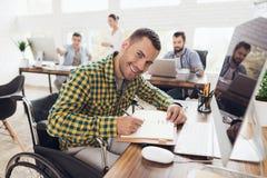 轮椅的一个人写与笔在笔记本 他在一个明亮的办公室工作 库存照片