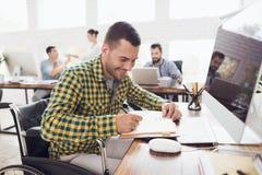 轮椅的一个人写与笔在笔记本 他在一个明亮的办公室工作 图库摄影
