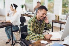 轮椅的一个人在电话写与笔在笔记本并且谈话 他在一个明亮的办公室工作 免版税库存图片