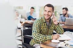 轮椅的一个人在电话写与笔在笔记本并且谈话 他在一个明亮的办公室工作 免版税库存照片