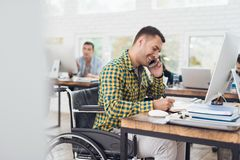 轮椅的一个人在电话写与笔在笔记本并且谈话 他在一个明亮的办公室工作 库存照片