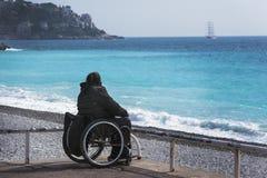 轮椅的一个女孩坐天蓝色的海的岸 美丽的蓝色海、山在阴霾和船在distanc 库存图片