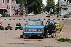 轮椅的一个年长人是在老汽车Zaporozhets GAZ 968旁边在Uglich 免版税库存照片