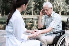 轮椅的一个年长人诉说头疼给医生 免版税库存照片