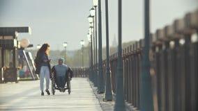 轮椅的一起走残疾的人她的码头的女朋友 股票视频