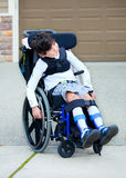 轮椅的七岁的两种人种的残疾男孩 库存照片