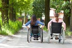 轮椅的两名妇女在公园 库存照片