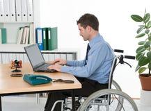 轮椅的人在办公室 免版税库存照片