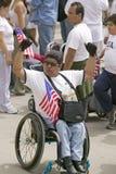 轮椅的人拿着美国标志 库存照片