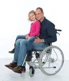 轮椅的人有女儿的 库存照片