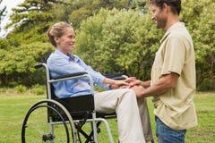 轮椅的可爱的妇女有下跪在她旁边的伙伴的 库存照片
