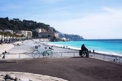 轮椅的女孩坐天蓝色的海的岸 美丽的蓝色海、一辆停放的自行车、山在阴霾和船i 免版税库存照片