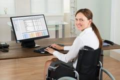轮椅的女实业家使用计算机在办公室 免版税库存照片