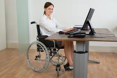 轮椅的女实业家,当研究计算机时 免版税库存照片