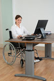 轮椅的女实业家,当研究计算机时 免版税库存图片