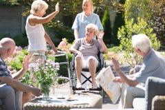 轮椅的妇女在庭院里 免版税库存图片