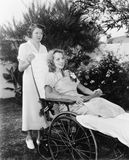 轮椅的妇女有护士的(所有人被描述不更长生存,并且庄园不存在 供应商保单那里w 库存图片