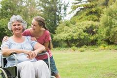 轮椅的孙女拥抱的祖母 免版税库存照片