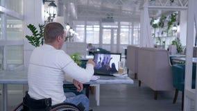 轮椅的学习者有残障的人在笔记本写笔记,当观看网上训练参加在桌上时 股票录像